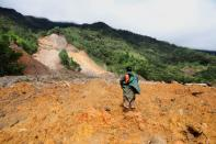 A soldier stands at an area hit by a mudslide, caused by heavy rains brought by Storm Eta, as the search for victims continue in the buried village of Queja