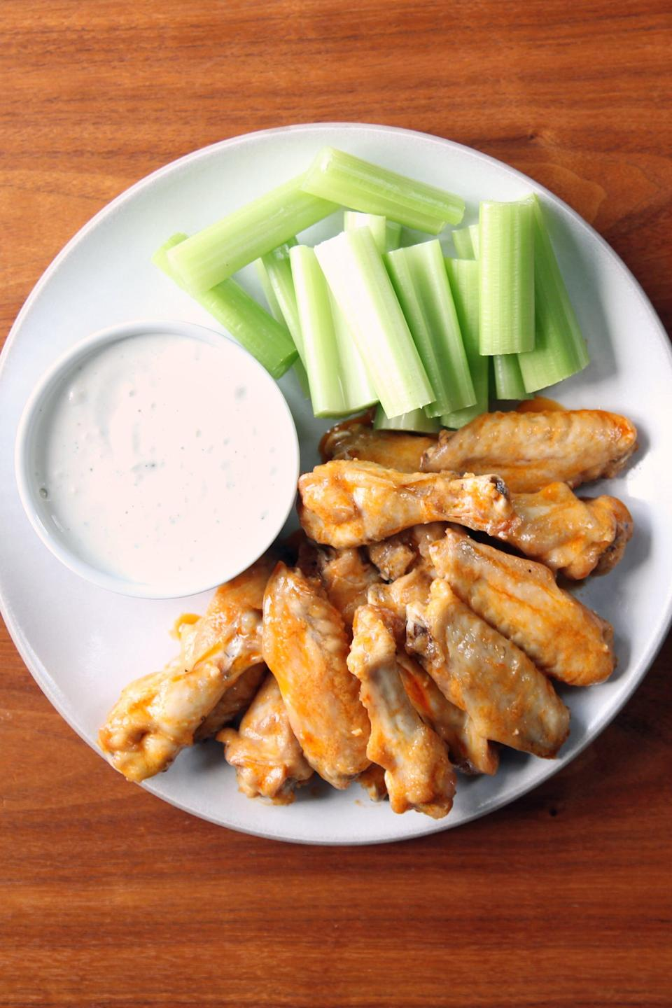"""<p>This easy buffalo chicken recipe is hassle-free and supertasty! Not to mention, these wings are baked not fried, so they are also lower in calories. Touchdown!</p> <p><strong>Get the recipe:</strong> <a href=""""https://www.popsugar.com/food/Baked-Buffalo-Chicken-Wings-Recipe-7257582"""" class=""""link rapid-noclick-resp"""" rel=""""nofollow noopener"""" target=""""_blank"""" data-ylk=""""slk:classic buffalo wings"""">classic buffalo wings</a> </p>"""