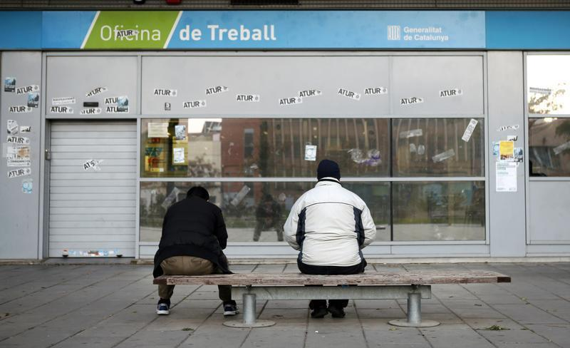 People wait for the opening of an employment office in Badalona