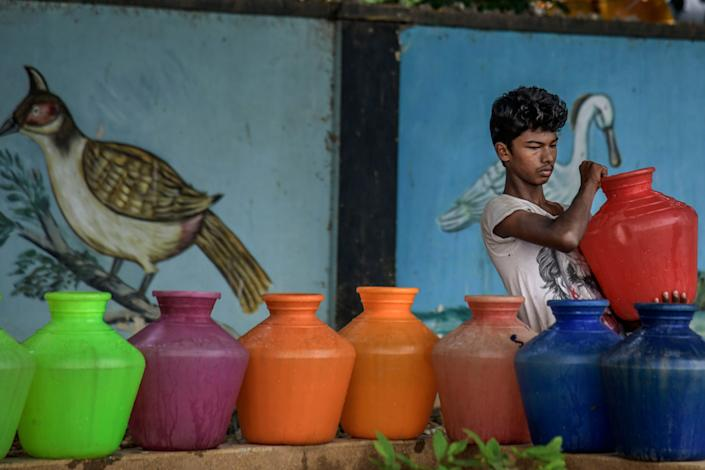 A boy carries water cans being filled at the Metro water filling station in the heart of Chennai on June 30, 2019. All four major reservoirs supplying water to the city had dried up. (Photo: Atul Loke via Getty Images)