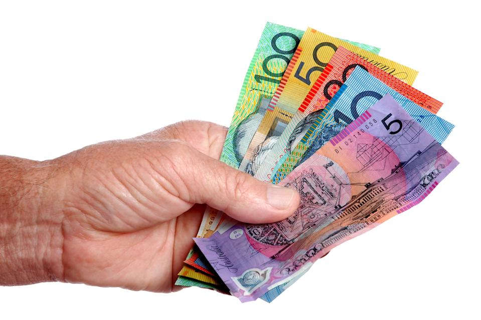 Australian dollar notes held in the hand.