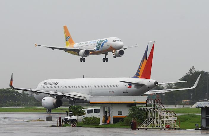 File Photo: A Cebu Pacific plane (top) preparing to land past a Philippine Airlines (PAL) plane (R) at Manila International Airport. (Photo: TED ALJIBE/AFP via Getty Images)