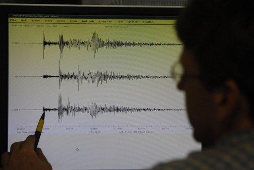 A seismologist looks at the data showing a strong earthquake