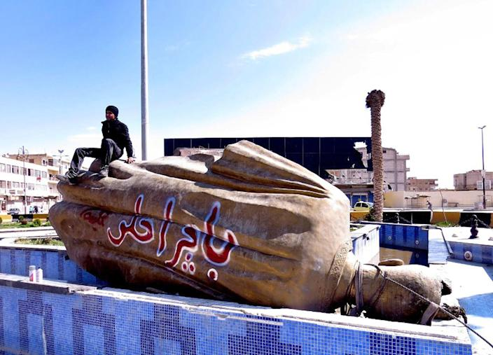 "FILE - In this Tuesday, March. 5, 2013 file citizen journalism image provided by Aleppo Media Center AMC which has been authenticated based on its contents and other AP reporting, shows a Syrian man sitting on a fallen statue of former Syrian President Hafez Assad in a central square in Raqqa, Syria. Since Raqqa fell under rebel control last week, opposition fighters have posted guards at government buildings to prevent looting, brought down the price of bread and opened a telephone hotline for residents to report security problems. Raqqa is shaping up as a test case for how rebels will administer their areas. Arabic on the fallen statue reads, ""tomorrow will be better."" (AP Photo/Aleppo Media Center AMC, File)"