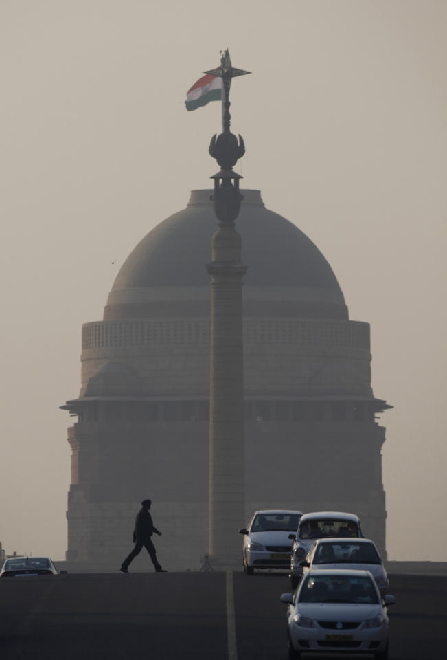 In this Thursday, Dec. 15, 2011 photo, a man walks by the Presidential Palace through haze caused by smog in New Delhi, India. A decade ago, plans for a metro and clean-fuel buses were hailed as New Delhi's answer to pollution. But air in the Indian capital is as dirty as ever - partly because its continued development has brought skyrocketing use of cars. (AP Photo/Saurabh Das)