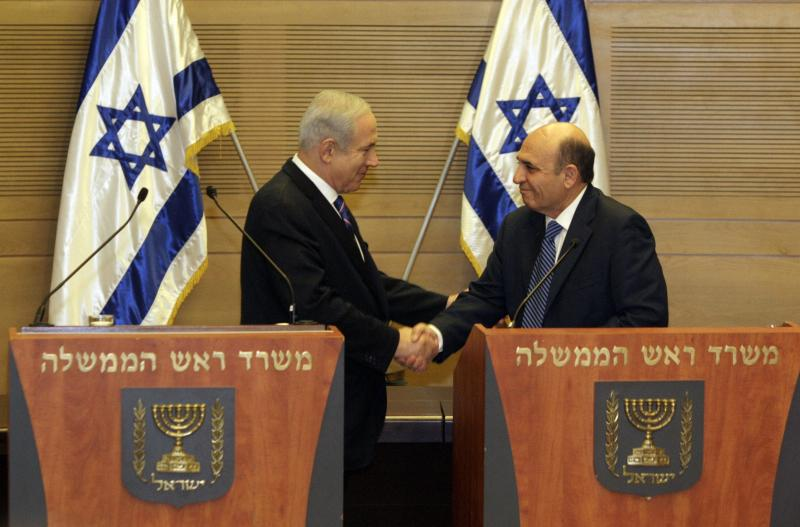 """Jerusalem : Israel's Prime Minister Benjamin Netanyahu, left, and Kadima party leader Shaul Mofaz shake hands before holding a joint press conference announcing the new coalition government, in Jerusalem, Tuesday, May 8, 2012. Netanyahu said Tuesday his new coalition government will promote a """"responsible"""" peace process with the Palestinians. AP/PTI(AP5_8_2012_000121A)"""