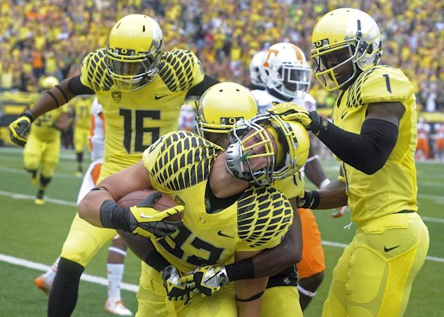 Oregon tight end John Mundt (83) is mobbed by teammates after scoring a touchdown during the first quarter of an NCAA college football game against Tennessee in Eugene, Ore., Saturday, Sept. 14, 2013. (AP Photo/Steve Dykes)