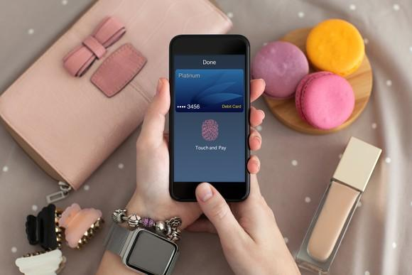 Hands holding a phone displaying the Apple pay concept.
