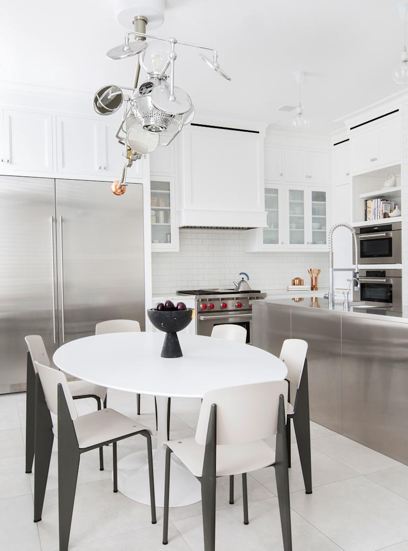 """An abundance of stainless steel, seen in the kitchen island and several appliances, gives the kitchen a """"super utilitarian feeling,"""" says Grehl. Midcentury furnishings both complement and counterbalance the sleek look."""