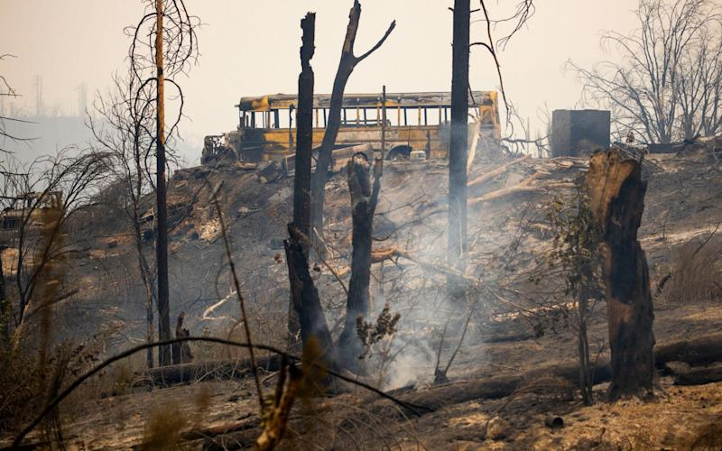 A burnt out school bus sit on a hill after the Bear Fire - Shutterstock