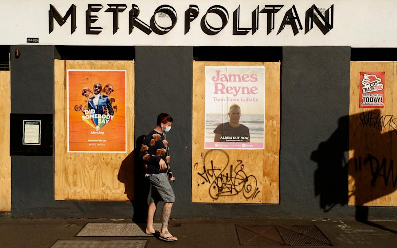 A man walks past a boarded up hotel in Melbourne