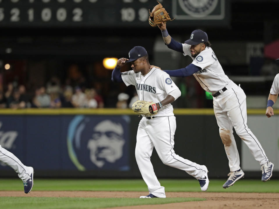 Seattle Mariners' J.P. Crawford, right, playfully taps Tim Beckham, left, with his glove as the Mariners celebrate their 10-2 win over the Detroit Tigers in a baseball game, Thursday, July 25, 2019, in Seattle. Beckham hit a grand slam in the game. (AP Photo/Ted S. Warren)