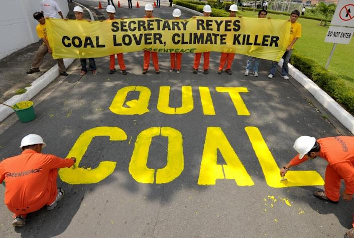 Greenpeace activists demonstrate on the driveway of the Department of Energy in Manila (AFP Photo/Jay Directo)