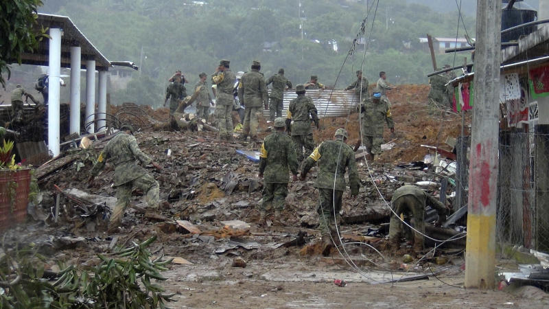 Soldiers search through mud and rubble for bodies, victims of a landslide in the town of La Pintada, Mexico, Saturday, Sept. 21, 2013. Dozens remained missing in La Pintada, where soldiers continued digging after a landslide caused by the one-two punch of storms Manuel and Ingrid, wiped out half of the town. (AP Photo)