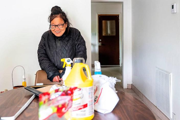 Despite an incredibly difficult and harrowing month, Helen Wong still keeps a smile on her face while a crew of several kind-hearted volunteers work on deep cleaning her home on Thursday afternoon in Lewiston.