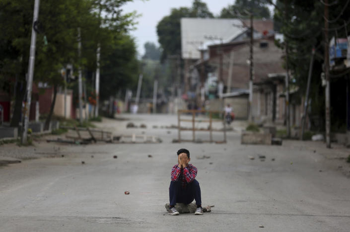 A protester covers his face as he sits on a rock during an anti-India protest in Srinagar, India, Friday, Aug. 9, 2019. The predominantly Muslim area has been under an unprecedented security lockdown and near-total communications blackout to prevent unrest and protests after India's Hindu nationalist-led government said Monday it was revoking Kashmir's special constitutional status and downgrading its statehood. (AP Photo/Altaf Qadri)