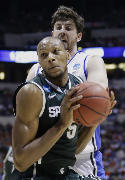 Michigan State forward Adreian Payne (5) drives the ball past Duke forward Ryan Kelly during the first half of a regional semifinal in the NCAA college basketball tournament, Friday, March 29, 2013, in Indianapolis. (AP Photo/Michael Conroy)