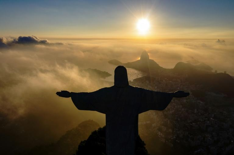 In this file photo taken in March 2021, the sun rises in front of the Christ the Redeemer statue in Rio de Janeiro, Brazil (AFP/CARL DE SOUZA)