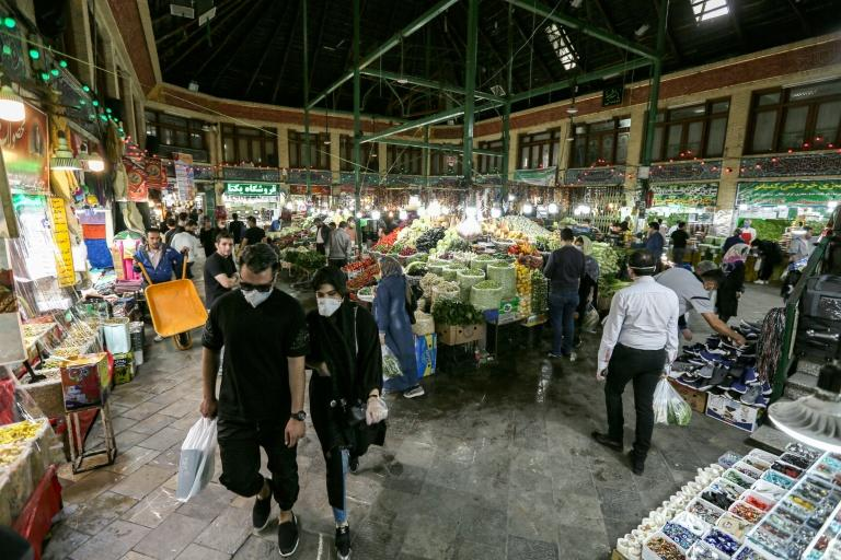 Shoppers clad in protective gear, including face masks and latex gloves, walk through Tajrish Bazaar in Iran's capital Tehran at the start of the Muslim holy month of Ramadan (AFP Photo/ATTA KENARE)
