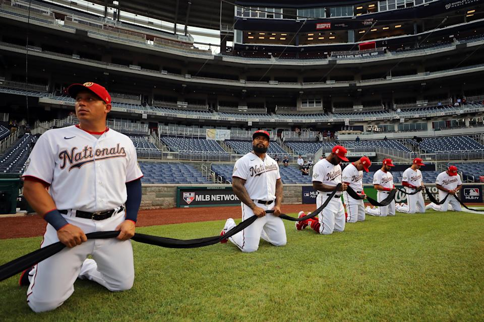 Nationals and Yankees player knelt while holding a black ribbon. (Photo by Alex Trautwig/MLB Photos via Getty Images)