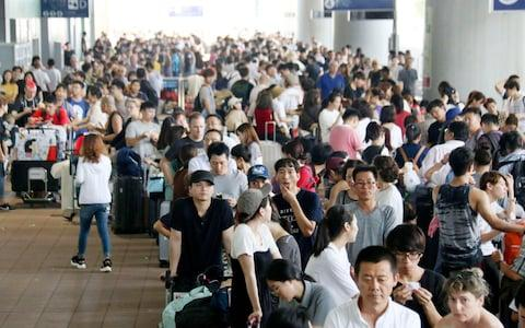 Stranded passengers queue up in lines to wait for special buses at Kansai International Airport  - Credit: AP