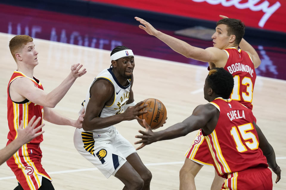 Indiana Pacers' Caris LeVert (22) looks for a shot between Atlanta Hawks' Bogdan Bogdanovic (13), Clint Capela (15) and Kevin Huerter during the second half of an NBA basketball game Thursday, May 6, 2021, in Indianapolis. (AP Photo/Darron Cummings)