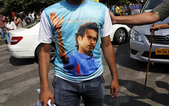 A fan wears a t-shirt with a portrait of Indian cricketer Sachin Tendulkar outside Wankhede Stadium to pay tribute to Tendulkar who retired today in Mumbai, India, Saturday, Nov. 16, 2013. Tendulkar's last day featured a cameo appearance bowling for a couple of overs, and a guard of honor from teammates as he walked from the field for the last time.Among his other prominent milestones include becoming the first man to score a double-century in limited-overs internationals (200 not out vs South Africa at Gwalior in 2010) and the first to reach 100 international centuries. (AP Photo/Rajanish Kakade)