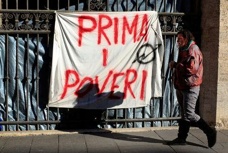 """Angela Grossi walks past a banner reading """"Poor first"""", hanging in a gate of the portico of the Basilica of the Santi Apostoli, where she lives after being evicted from an unused building along with other families in August 2017, in Rome, Italy January 29, 2018.   REUTERS/Tony Gentile"""