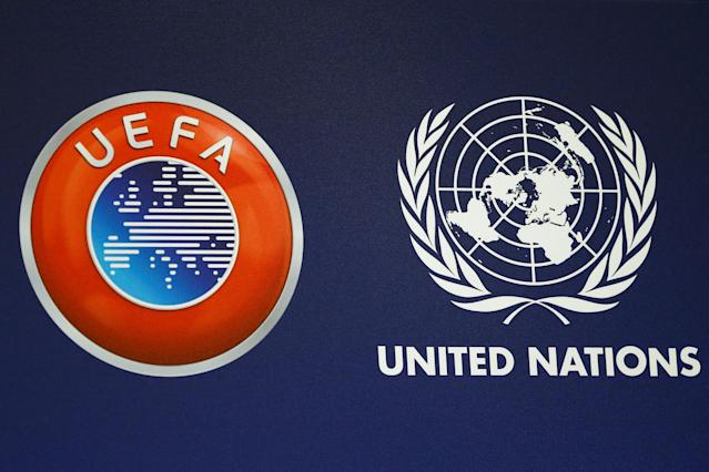 The Union of European Football Associations (UEFA) logo and the United Nations emblem are pictured during a news conference about a charity football match at the U.N. headquarters in Geneva, Switzerland February 13, 2018. REUTERS/Pierre Albouy