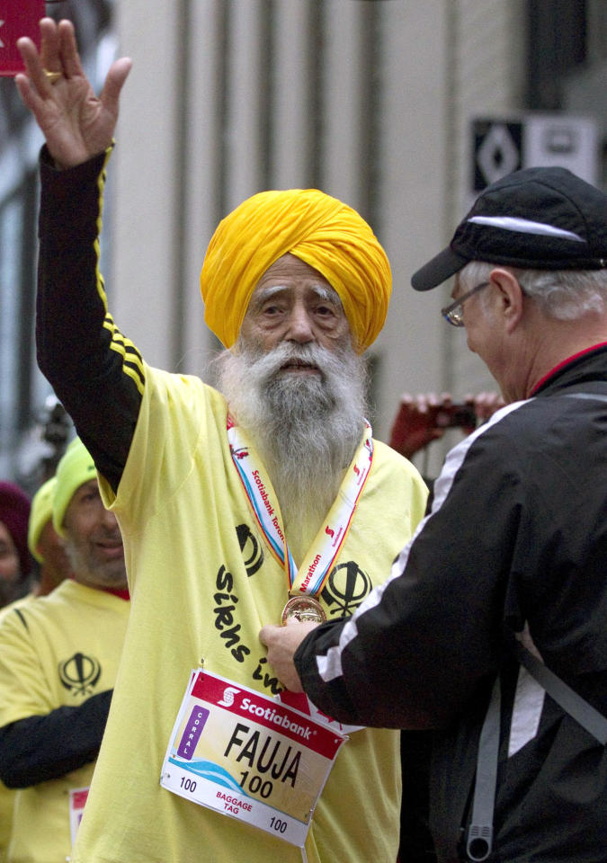 Fauja Singh, 100, receives a finishing medal after crossing the line in the Toronto Waterfront Marathon in Toronto on Sunday, Oct. 16, 2011. (AP Photo/The Canadian Press, Frank Gunn)