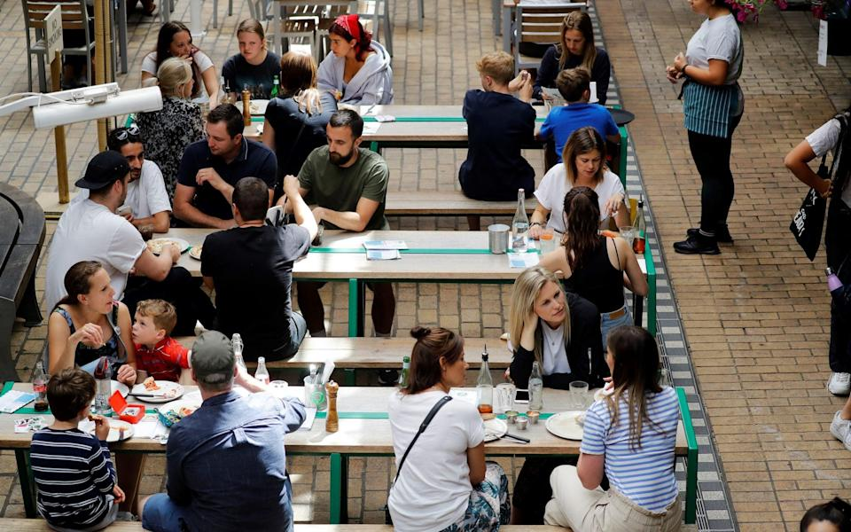 A server takes a customer's order as diners sit at tables outside a restaurant in London - TOLGA AKMEN/AFP