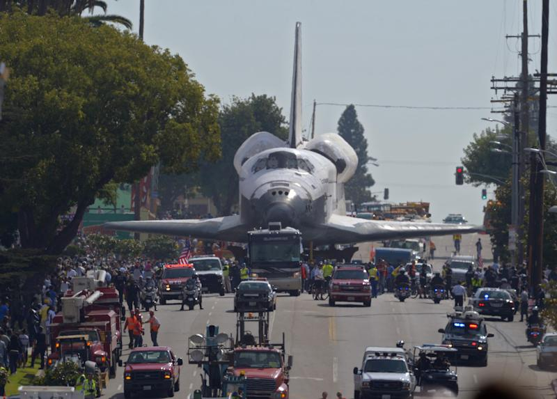 The space shuttle Endeavour is slowly moved down Crenshaw Blvd., Saturday, Oct. 13, 2012, in Los Angeles. The shuttle is on its last mission — a 12-mile creep through city streets. It will move past an eclectic mix of strip malls, mom-and-pop shops, tidy lawns and faded apartment buildings. Its final destination: California Science Center in South Los Angeles where it will be put on display. (AP Photo/Mark J. Terrill)