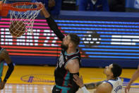 Memphis Grizzlies center Jonas Valanciunas, left, dunks in front of Golden State Warriors forward Juan Toscano-Anderson during the first half of an NBA basketball game in San Francisco, Sunday, May 16, 2021. (AP Photo/Jeff Chiu)