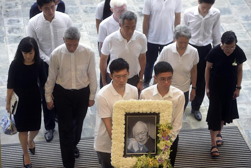 The family of the late Lee Kuan Yew arrives at the start of the state funeral at the University Cultural Center,  Sunday, March 29, 2015 in Singapore.  During a week of national mourning that began Monday after Lee's death at age 91, some 450,000 people queued for hours for a glimpse of Lee's coffin at Parliament House. A million people visited tribute sites at community centers across the island and leaders and dignitaries from more than two dozen countries attended the state funeral. (AP Photo/Joseph Nair)