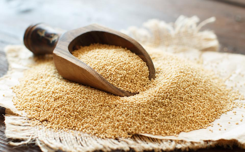 Raw Organic Amaranth grainwith a spoon on a wooden table