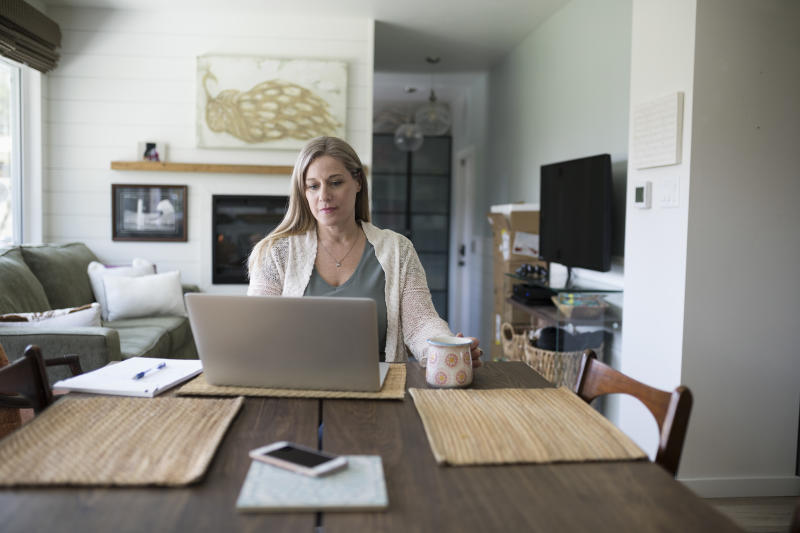 Woman working from home, using laptop in dining room