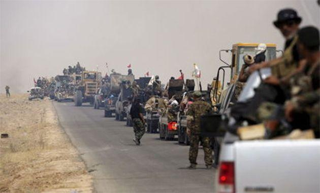 Shi'ite paramilitaries riding military vehicles travel from Lake Tharthar toward Ramadi to fight against Islamic state militants, west of Samarra, Iraq May 27, 2015. REUTERS/Stringer
