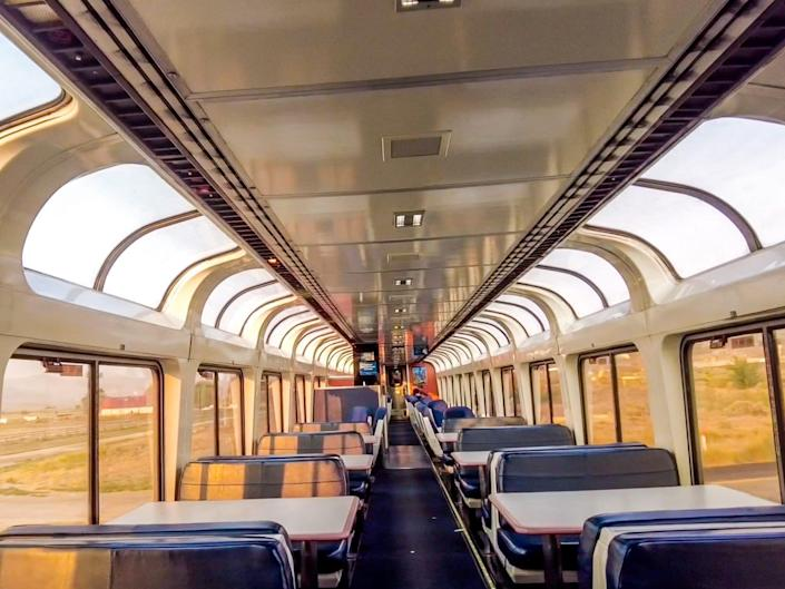 A view of the Amtrak observation car, which is full of windows and blue seats