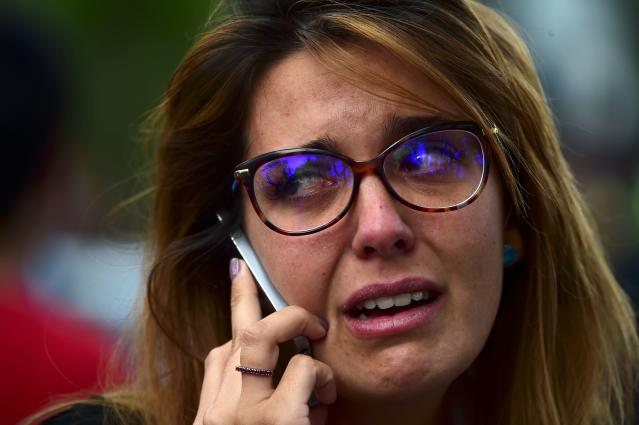 <p>A woman cries on the phone as the search for survivors continues in Mexico City on Sept. 20, 2017 a day after a strong quake hit central Mexico. (Photo: Ronaldo Schemidt/AFP/Getty Images) </p>