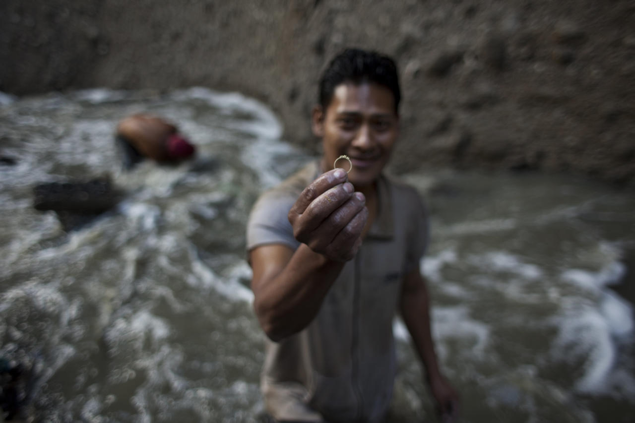 """In this photo taken Thursday Oct. 6, 2011, a man holds up a gold ring he found as he was searching for scrap metal in contaminated water at the bottom of one of the biggest trash dumps in the city, known as """"The Mine,"""" in Guatemala City. Hundreds of informal workers descend daily into the mounds of the landfill and the rushing waters that come from a storm tunnel and a sewer at the bottom of a gorge to search for scrap metal to sell. This activity known locally as """"mining"""" is extremely dangerous due to mud slides and collapses, but earns many of them about 150 quetzals ($20 dollars) a day, nearly twice the minimum daily wage. AP Photo/Rodrigo Abd)"""