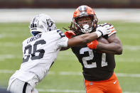 Cleveland Browns running back Kareem Hunt (27) tries to break a tackle by Las Vegas Raiders cornerback Nevin Lawson (26) during the first half of an NFL football game, Sunday, Nov. 1, 2020, in Cleveland. (AP Photo/Ron Schwane)