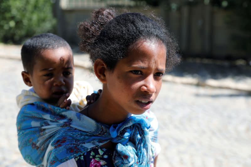 Mibrak Hailu, who says her parents were killed by Eritrean soldiers carries one of her five siblings, in the Tigray region