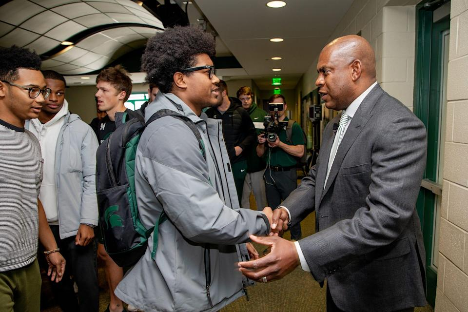 Mel Tucker greets MSU linebacker Antjuan Simmons before Tucker was introduced as MSU's new head football coach on Feb. 12.