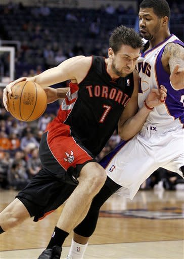 Toronto Raptors' Andrea Bargnani (7), of Italy, drives against Phoenix Suns' Ronnie Price during the first half of an NBA basketball game, Tuesday, Jan. 24, 2012, in Phoenix. (AP Photo/Matt York)