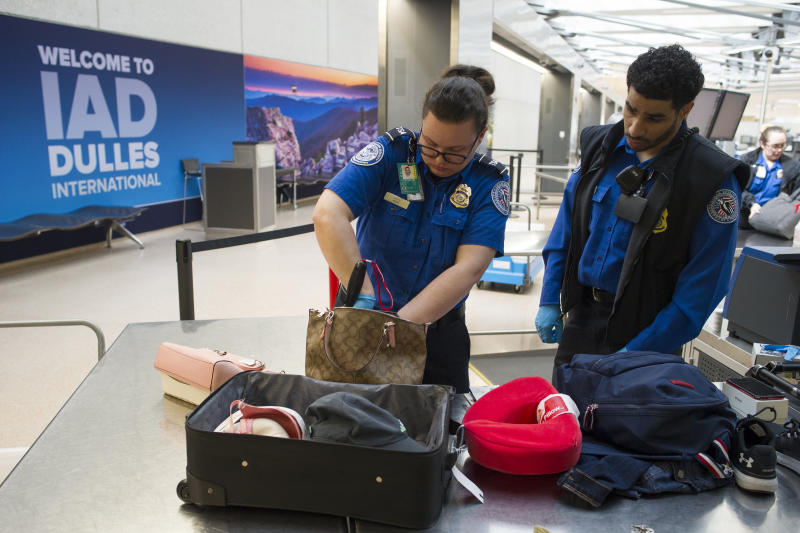 Transportation Security Administration (TSA) Officers search handbags which were packed in a suitcase at a checkpoint at Dulles International Airport in Dulles, Va., Tuesday, March 26, 2019. (AP Photo/Cliff Owen)
