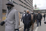 FILE - In this Monday, April 19, 2021 file photo, Ben Crump, left, attorney representing George Floyd's family, walks with the Rev. Al Sharpton, center, and Floyd's brothers Terrence Floyd, center left, and Rodney Floyd, center right, outside of the Hennepin County Government Center in Minneapolis, before the murder trial against former Minneapolis police officer Derek Chauvin advances to jury deliberations. (AP Photo/Julio Cortez)