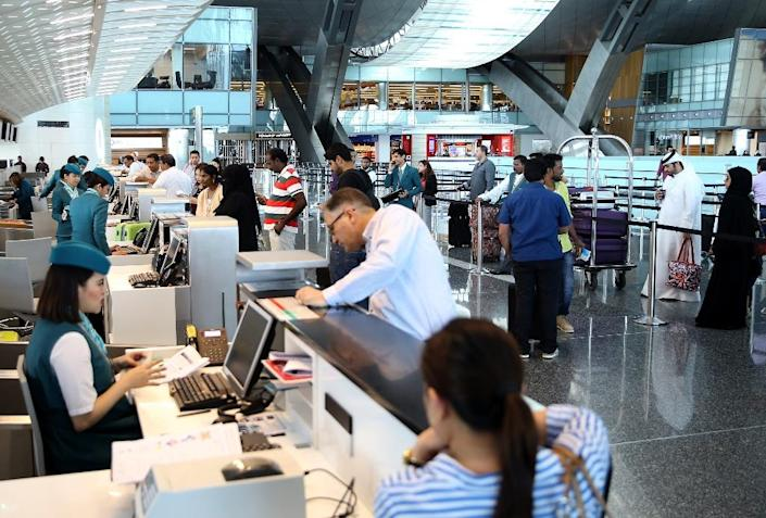 Passengers check-in at Hamad International Airport in Doha. Qatar Airways has made Doha a global hub in just a few years, but barring it from Gulf states' airspace could threaten its position as a major transcontinental carrier (AFP Photo/STRINGER)