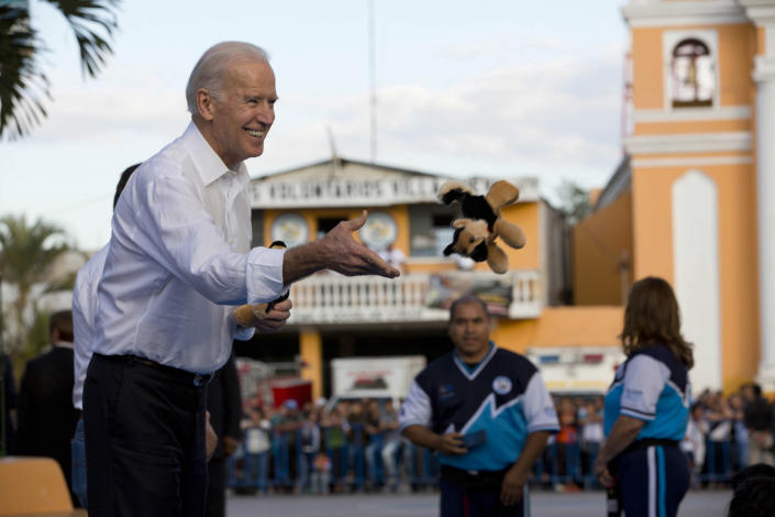 U.S. Vice President Joe Biden tosses a stuffed animal to children in Villa Nueva on the outskirts of Guatemala City, Tuesday, March 3, 2015. Biden gave a toy to each child from a group who gave him a karate demonstration on the second day of his trip to meet with Central American leaders regarding immigration issues. (Moises Castillo/AP Photo)
