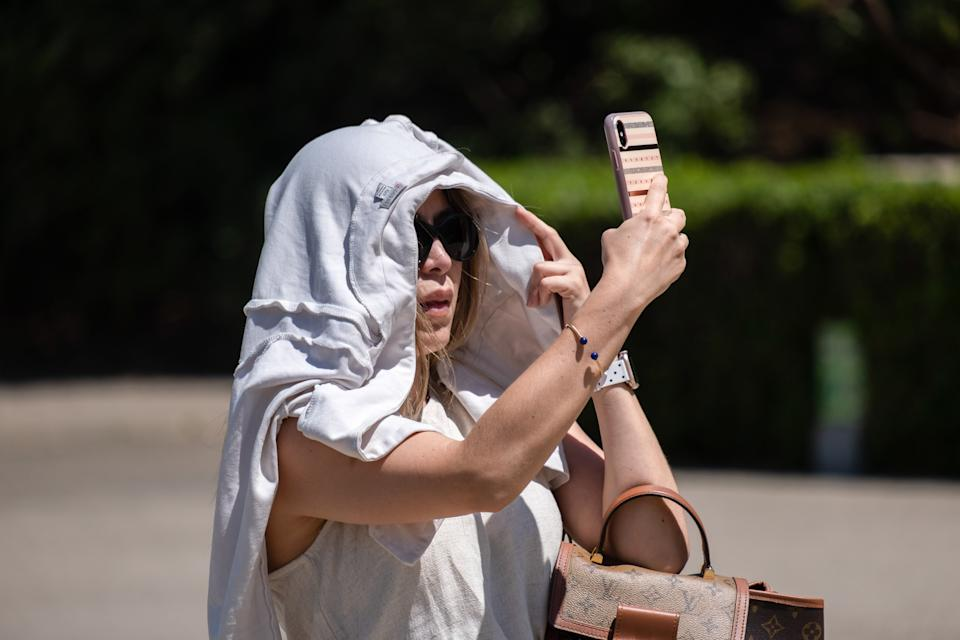 BARCELONA, SPAIN - 2021/07/18: A tourist is seen covering her head from the sun and heat in the museum area of Montjüic mountain. According to the State Meteorological Agency (AE.MET), an increase in temperatures is expected in Catalonia. For Barcelona the warning will be at an orange level with temperatures between 30 and 39 degrees centigrade. (Photo by Paco Freire/SOPA Images/LightRocket via Getty Images)