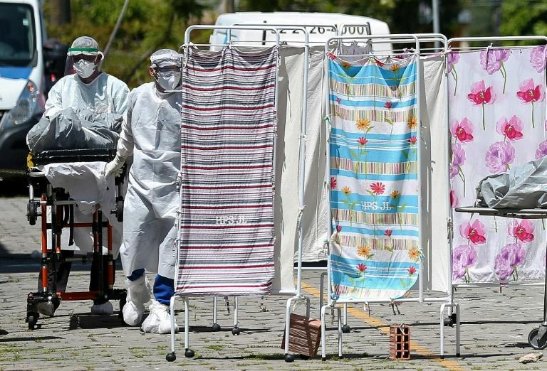 Healthcare workers in protective clothing transport the body of a COVID-19 victim outside Joao Lucio Hospital in Manaus, Brazil, on April 21, 2020 (AFP Photo/MICHAEL DANTAS)